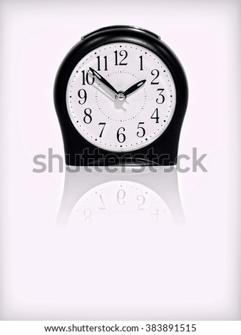 Alarm clock with reflection on white background.Purple toned image. - stock photo