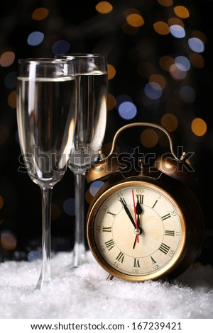 Alarm clock with snow and stemware on table on bright background