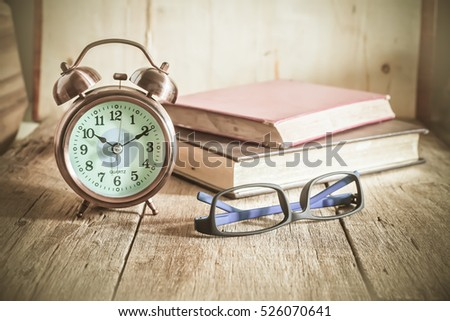 Alarm clock with text book on wood table