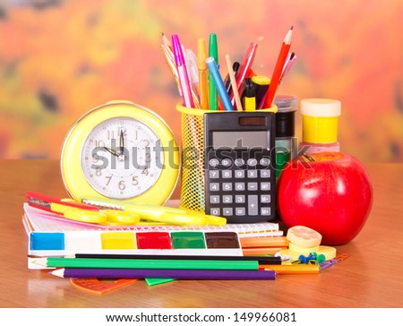 Alarm clock, writing materials, calculator, scissors, paints and an apple, on a table