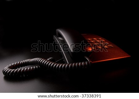 Alarm signal - phone under red light in the dark - stock photo