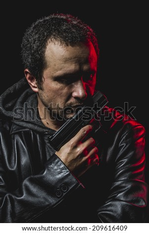 alarm, thief with gun in hand. man in leather jacket
