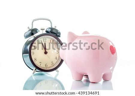 Alarmclock with piggybank on white background - stock photo