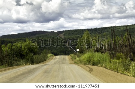 Alaska, raw gravel road to Arctic Circle with pipeline on the side - stock photo