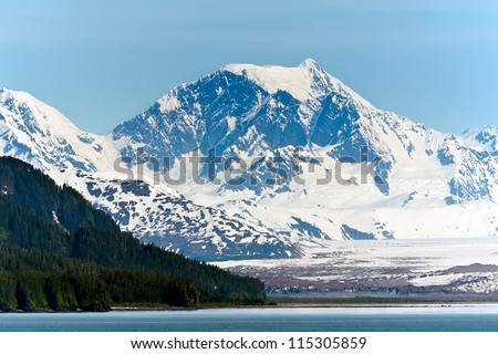 Alaska's snow capped mountain range and thick forest along the Inside Passage - stock photo