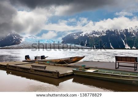 Alaska wilderness landscape: Taku Glacier and River under a stormy sky. A boat dock is in the foreground. Location: Southeastern Alaska near Juneau. - stock photo