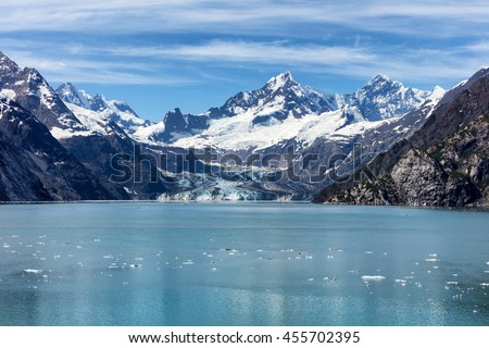 Alaskan glacier flowing into bay with floating ice and water in forefront.