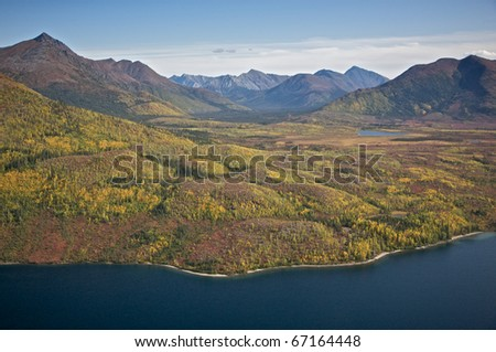 Alaskan mountain valley with hills meeting a blue lake. - stock photo