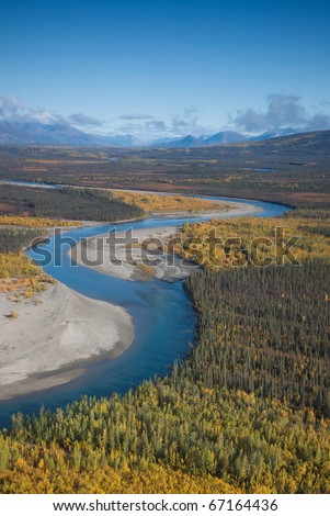 Alaskan river flowing through a mountain valley. - stock photo