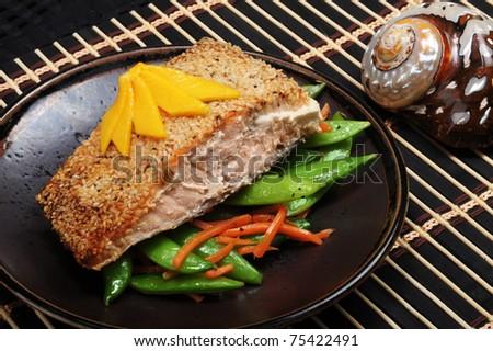Alaskan Salmon with sesame crust, green split peas and mango on top. - stock photo