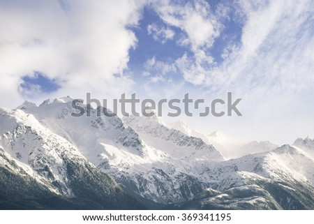 Alaskan snow covered mountain range with clouds and blue sky. - stock photo