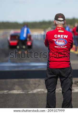 ALASTARO, FINLAND - JULY 7: A crew member is watching preparation for start at the start line of a strip. Image taken in Alastaro, Finland - Nitro Nationals Championships in July 7th 2013. - stock photo
