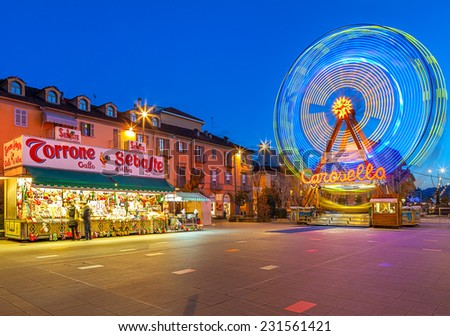 ALBA, ITALY - DECEMBER 30, 2013: Illuminated observation wheel and mobile stall with sweets on city square as part of traditional Christmas and New Year celebrations. - stock photo