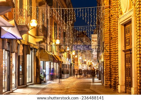 ALBA, ITALY - DECEMBER 30, 2013: Pedestrian street in old town illuminated and decorated for Christmas and New Year holidays. This area is very popular with locals and tourists visiting Alba. - stock photo
