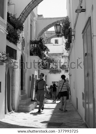 ALBEROBELLO, ITALY - CIRCA AUGUST 2009: Tourists visiting the historical town in black and white