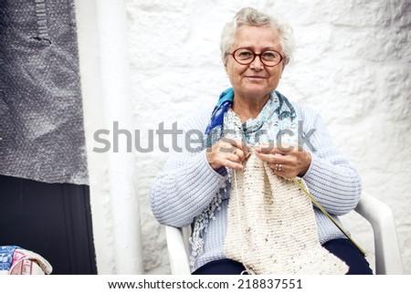 ALBEROBELLO, ITALY - OCTOBER 31, 2013: Old woman kntting in Alberobello on October 31, 2013, Italy - stock photo