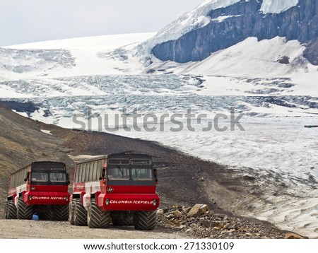 ALBERTA, CANADA - APR 15, 2015: Ice Explorers, designed for glacial travel, take tourists onto the surface of the Athabasca Glacier in the Columbia Icefields, Canada. - stock photo