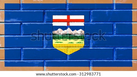 Alberta flag painted on old brick wall texture background - stock photo