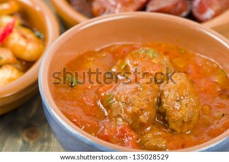 Albondigas a la jardinera (Meatballs in tomato sauce). Traditional Spanish tapas dish. - stock photo