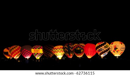 ALBUQUERQUE - OCTOBER 10.  Balloons are inflated and glowing  during the Dawn Patrol Show at the Albuquerque International Balloon Fiesta on the morning of October 10, at Albuquerque, NM - stock photo