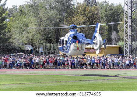 ALCALA DE HENARES, SPAIN - AUGUST 29th 2015: Unidentified people are watching a helicopter taking off, of spanish police, with parachutists inside, in Alcala de Henares, on August 29th 2015. - stock photo