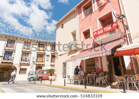ALCALALI, SPAIN- AUGUST 23; Spanish village scene man crosses street while women enjoy morning drink in shade outside small Spanish village bar August 23, 2016 in Alcalali Costa Blanca, Spain