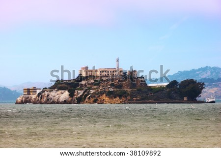 Alcatraz Island and Prison in San Francisco Bay in late afternoon with a ferry on the right side. - stock photo