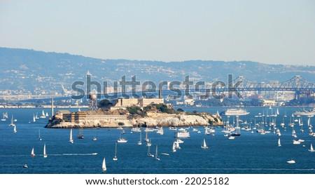 Alcatraz Island and Prison in San Francisco Bay on a sunny and hazy day with many boats around - stock photo