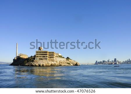 Alcatraz island in San Francisco Bay at sunset from the bay looking towards San Francisco - stock photo
