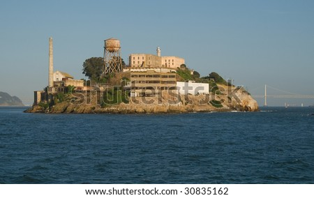Alcatraz Island with San Francisco Bay Bridge and Treasure Island in Background - stock photo