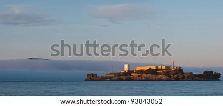 Alcatraz Prison. Image of Alcatraz Prison at sunset with fog coming in to San Francisco Bay. - stock photo