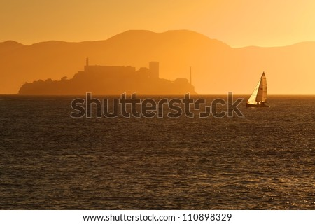 Alcatraz silhouette with boat during sunset in San Francisco, California - stock photo