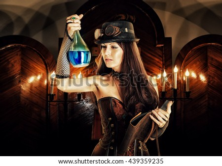 alchemist. Beautiful brunett girl witch wearing steampunk style prepares a potion or poison in a secret occult lab and reads a magical book of spells