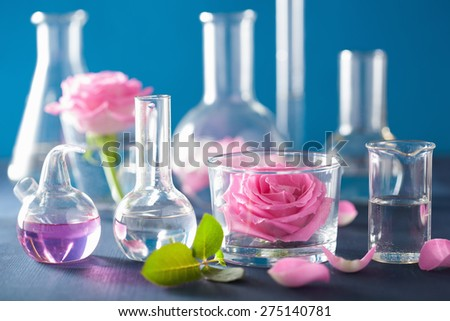 alchemy and aromatherapy set with rose flowers and chemical flasks - stock photo