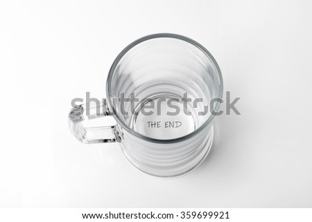 "alcohol addiction concept - empty glass with ""the end"" text on the bottom - stock photo"