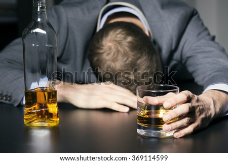 alcohol addiction - drunk businessman holding a glass of whiskey - stock photo