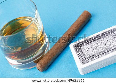alcohol and cigar on blue background - stock photo