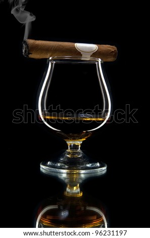 alcohol and smoking a cigar on a black background - stock photo