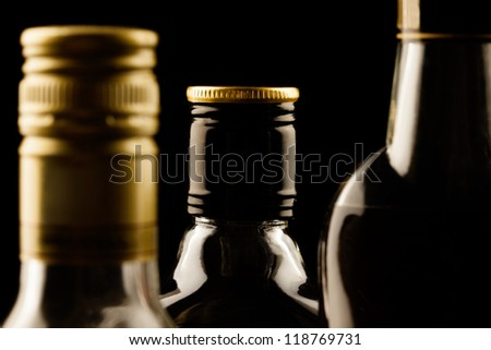 Alcohol bottles close-up background. Low aperture shot, focus on central bottle - stock photo