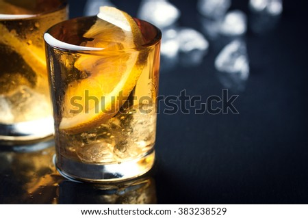 Alcohol cocktail with brandy, whiskey, lemon and ice in small glasses with place for text