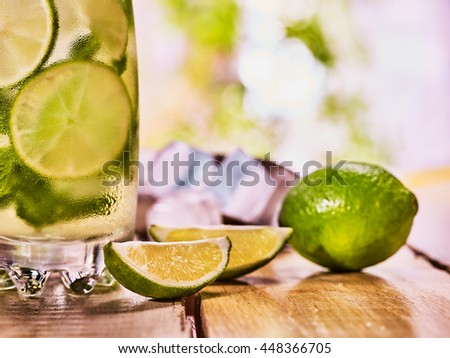 Alcohol drink. On wooden boards is part of glass with alcohol drink and ice cubes. Drink number thirty nine cocktail mohito and scoop ice and quartered lime. Country life cocktail . Light background.