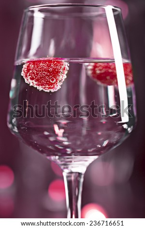 Alcohol drink with raspberry on the magenta blurred background - stock photo