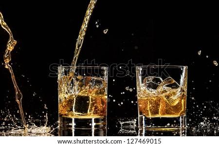 Alcohol drinks with splashes, isolated on black background - stock photo