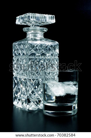 Alcohol in a glass in front of bottle - stock photo