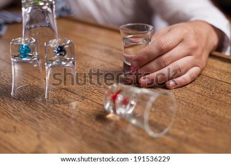 Alcohol. Man all alone drinking vodka at a bar. - stock photo