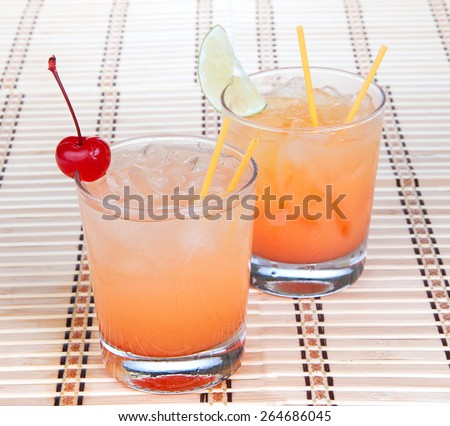 Alcohol margarita cocktails or long island Iced tea with lime in short cocktail glasses isolated on a white background - stock photo