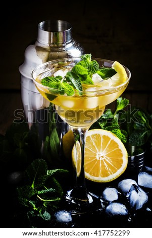 Alcoholic cocktail daiquiri with lemon and mint, dark background, selective focus - stock photo