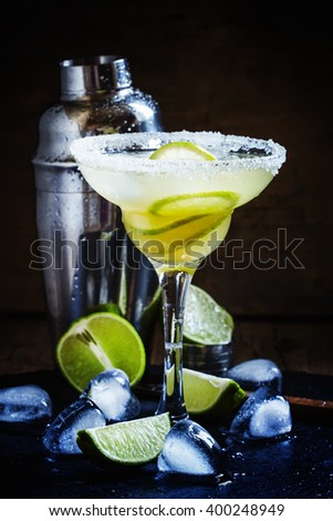 Alcoholic cocktail daiquiri with white rum, sugar syrup, lime juice and ice, black background, selective focus - stock photo