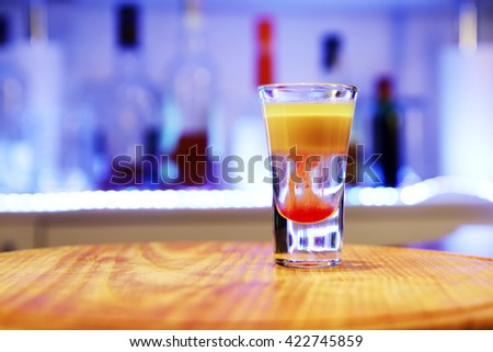 Alcoholic cocktail, drinks shot on a wooden board.Called Hiroshima Nagasaki. Good cocktail booze with decor composition in bar. Different layers of alcohol vodka, liqueur, whiskey and chasers. - stock photo