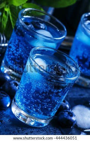 Alcoholic cocktail French soda, with liqueur, lime juice, sugar and ice, decorated with blueberries and mint, dark background, selective focus - stock photo